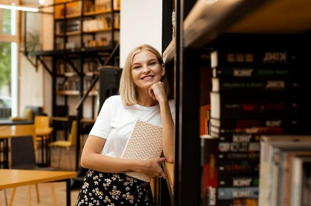 図書館でポーズをとるかなり若い女性 無料写真