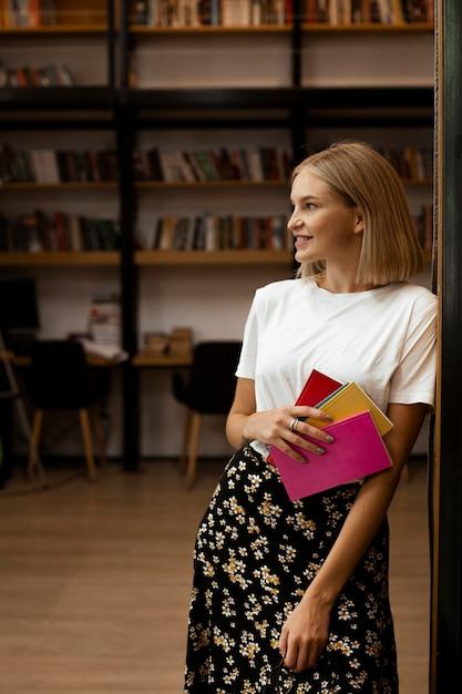 Bella giovane donna in posa in biblioteca Foto Gratuite