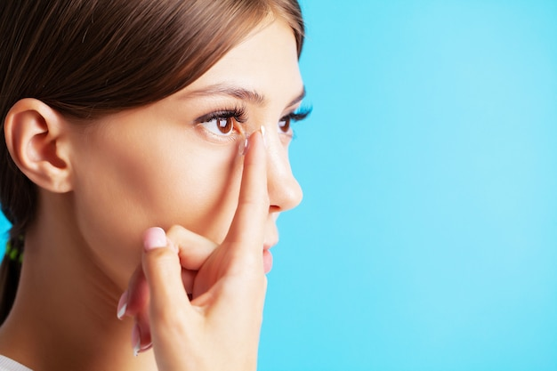 Pretty young woman puts on contact lenses for eyesight Premium Photo