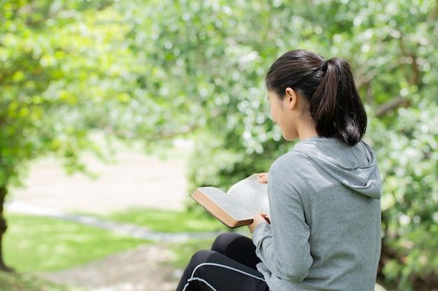 公園で聖書を読んでかなり若い女性。本を読んでいる。神の聖書の概念は信仰と霊性に基づいています。 Premium写真