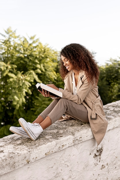 Pretty young woman reading a book outdoors Free Photo