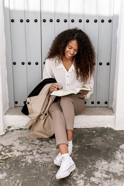 Pretty young woman reading a book outside Free Photo