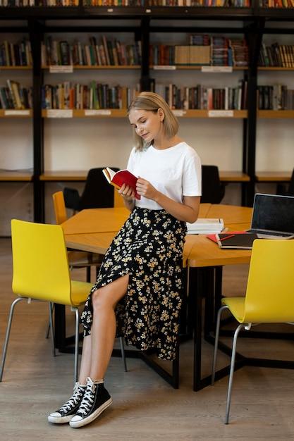 Donna abbastanza giovane che legge un libro Foto Gratuite