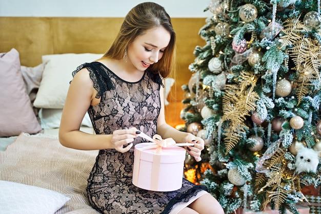 Довольно молодая женщина получает рождественские подарки против елки. Premium Фотографии