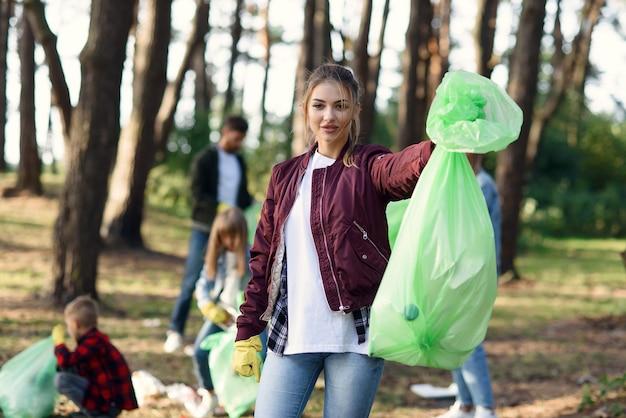 かなり若い女性は、公園でゴミを拾っている彼の友人のボランティアの背景に完全なゴミパックを示しています。 Premium写真