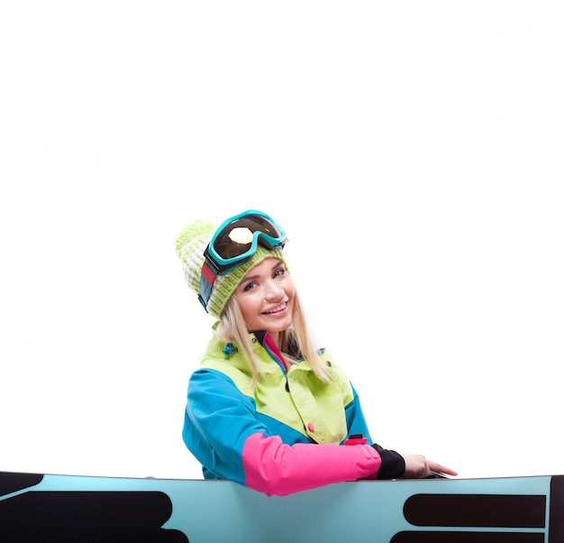 Pretty young woman in ski outfit sit near snowboard Premium Photo