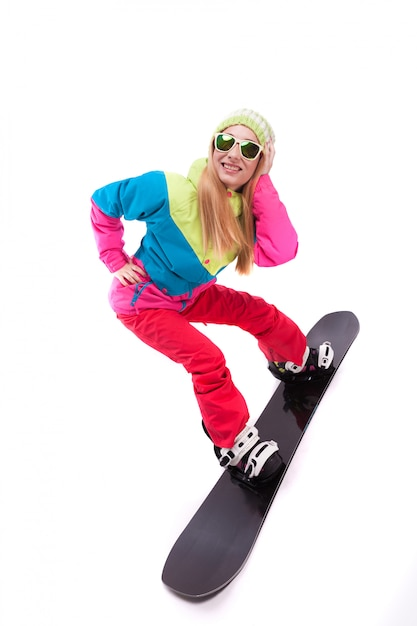 Pretty young woman in ski outfit and sunglasses ride snowboard Premium Photo
