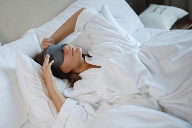 Довольно молодая женщина спит в белой кровати с маской для сна на ее лице Premium Фотографии