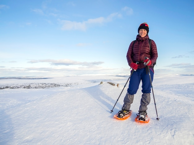 Pretty, young woman snowshoeing and enjoying splendid winter weather with abundance of snow Premium Photo