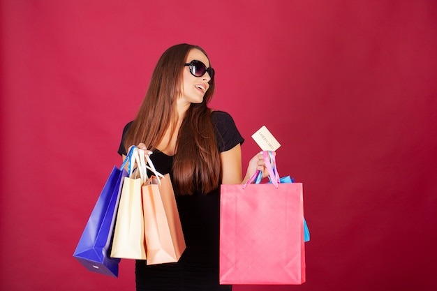 Pretty young woman stylishly dressed in black with bags after shopping Premium Photo