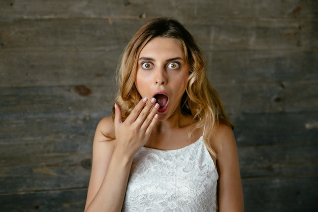 Pretty young woman surprised about something, covering her open mouth by hand Free Photo