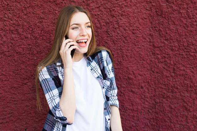 Pretty young woman talking on cellphone with mouth open against red wall Free Photo