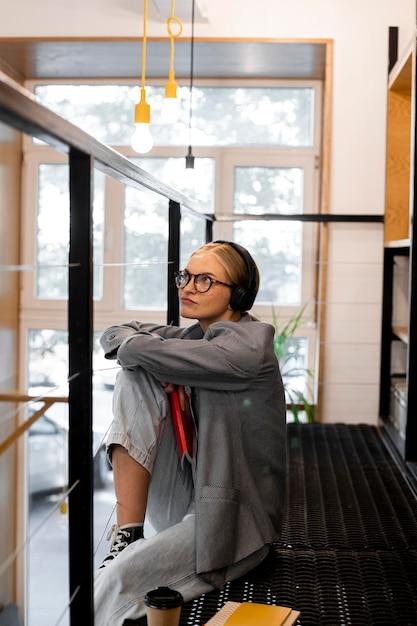 Donna abbastanza giovane che pensa alla biblioteca Foto Gratuite
