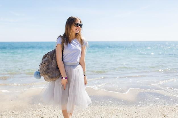 バッグを持つかなり若い女性が海の近くに立っています。 無料写真