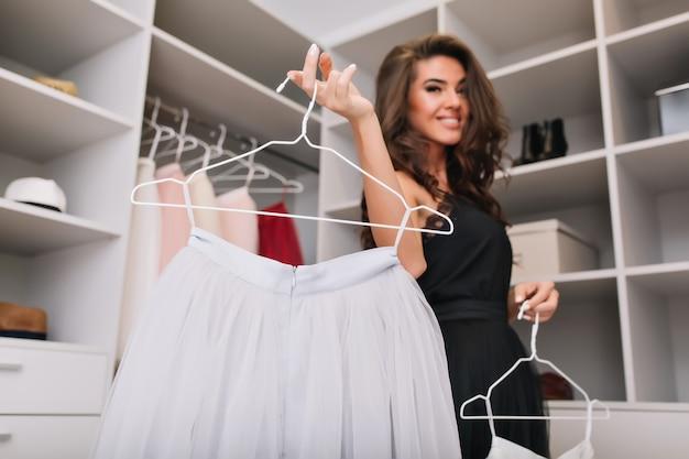 Довольно молодая женщина с каштановыми вьющимися волосами, держащая белую красивую юбку на вешалке, счастлива иметь красивую одежду. роскошный шкаф. модель с модным взглядом, в черном элегантном платье. Бесплатные Фотографии