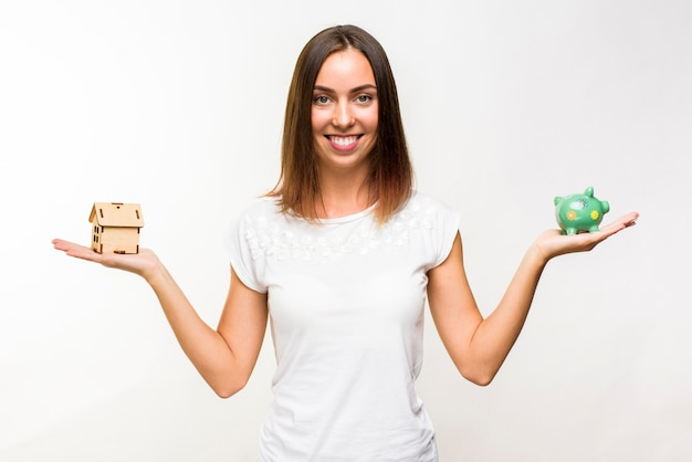 Pretty young woman with a cottage and a piggy bank Free Photo