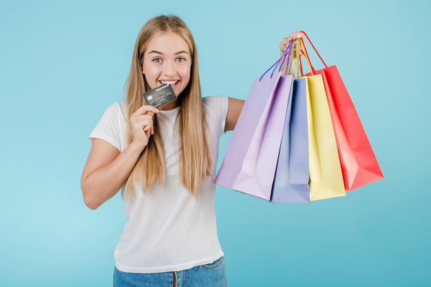 Pretty young woman with credit card and colorful shopping bags isolated over blue Premium Photo