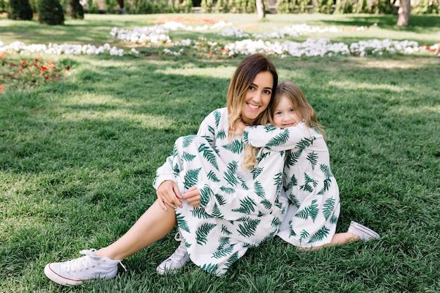Довольно молодая женщина с маленькой дочкой сидят на траве в солнечном свете Бесплатные Фотографии