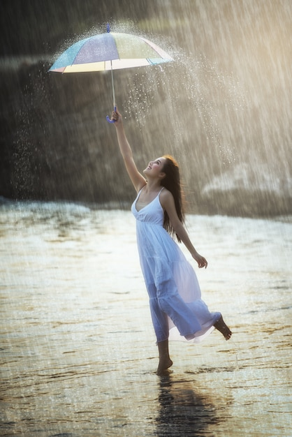 Pretty young woman with rainbow umbrella, under summer rain Premium Photo
