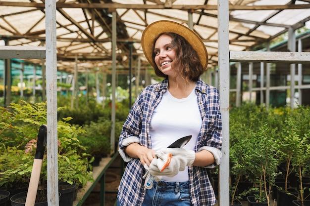温室で働くかなり若い女性 Premium写真