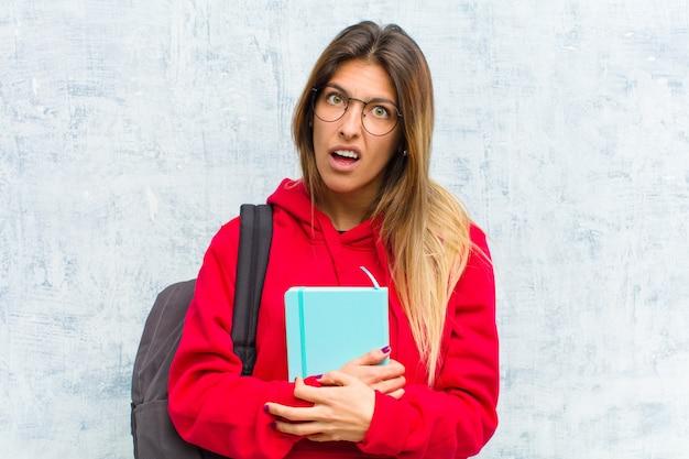 予想外の何かを見て愚かな、pretty然とした表情で困惑し、混乱している若いかなり学生 Premium写真