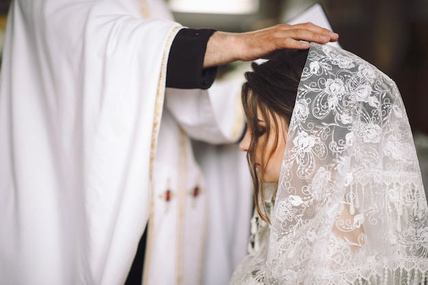 Priest blesses bride during the ceremony in church Free Photo