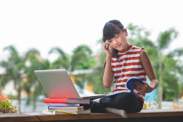 アジアの小学生が座って、home.online教育コンセプトから離れた場所で勉強する Premium写真