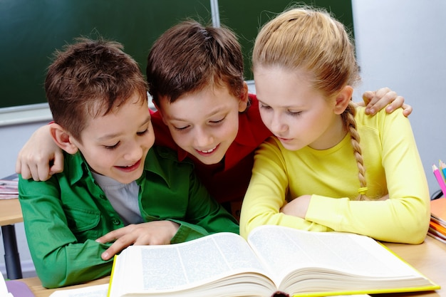 Primary students reading a yellow book with blackboard background Free Photo