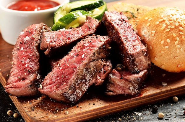 Prime black angus steak burger near bun and sauce Premium Photo