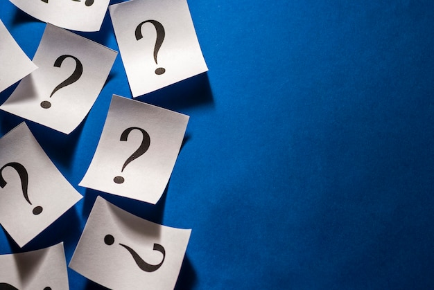 Printed question marks on white cards over blue Premium Photo