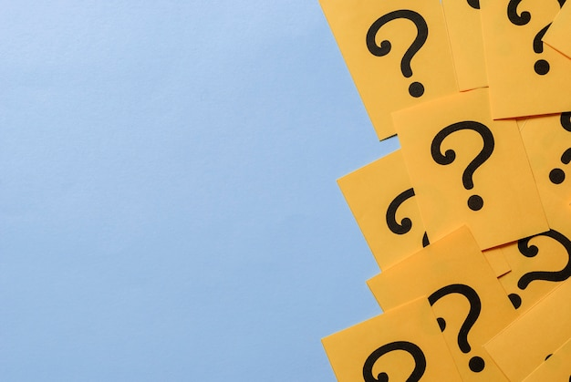 Printed question marks on yellow paper or card Premium Photo