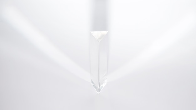 A prism dispersing sunlight on a white background Free Photo