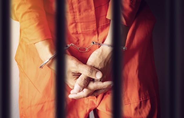 Prisoner hands in handcuffs behind the prison Premium Photo