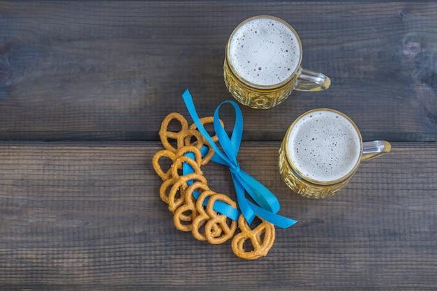 Концепция октябрьского фестиваля. пивная кружка с закусками из соли pritzels, bretzel и голубой лентой на темном деревянном столе. Premium Фотографии