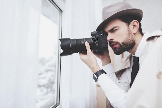 Частный детектив фотографирует в окне. Premium Фотографии
