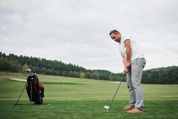 코스 골프 클럽을 목표로 프로 골프 선수. 타격을하려고 녹색 퍼 팅에 남성 골퍼 프리미엄 사진