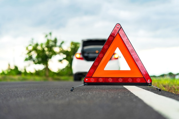 Problems car and a red triangle warning sign on the road Premium Photo