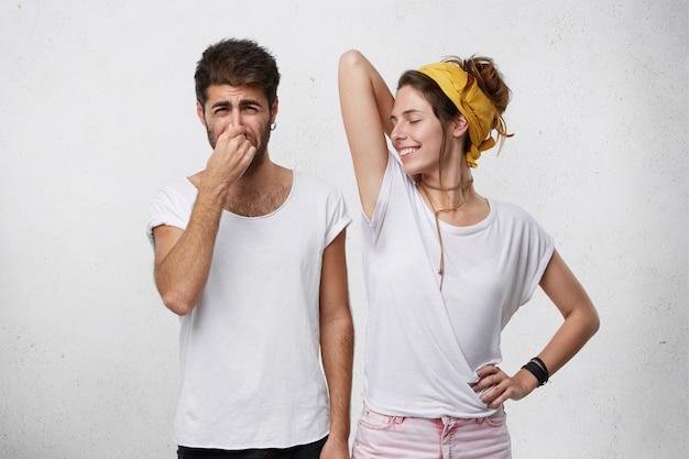 Problemi con l'odore del corpo. uomo disgustato che si pizzica il naso sentendo cattivo odore o puzza che esce da una ragazza sorridente attraente, che alza il braccio, mostrando la maglietta bagnata a causa del sudore delle ascelle Foto Gratuite