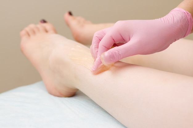 Procedure of hair removing on leg beautiful woman with sugar paste or wax honey and pink gloves hand Premium Photo