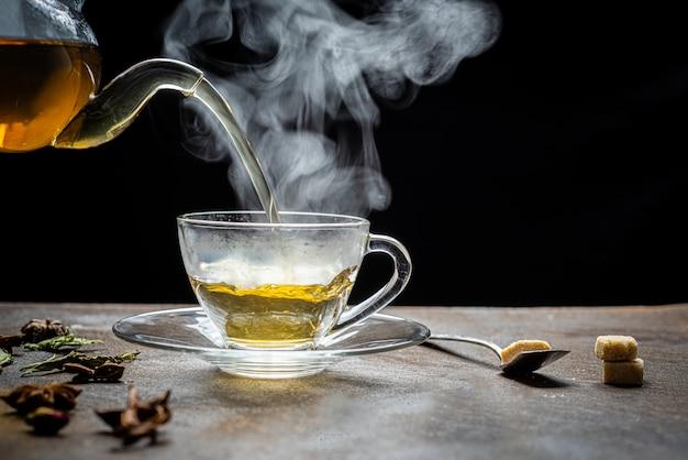Process brewing tea,cup of freshly brewed fruit and herbal tea, dark mood. Premium Photo