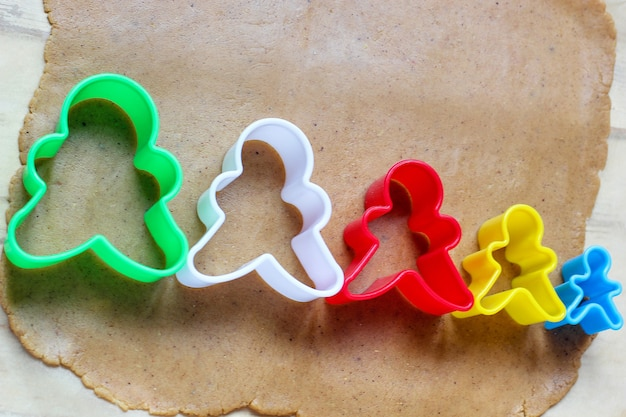 Process of dealing with gingerbread man cookies, use red gingerbread man mold cutting gingerbread dough on baking paper around colorful cookie cutters on white wooden table. top view Free Photo