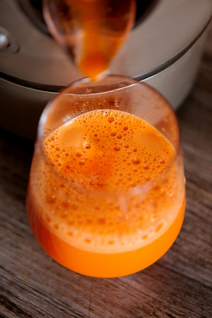 Process of making juice in a juicer, process preparation of fresh juice in juicer, carrot juice Premium Photo