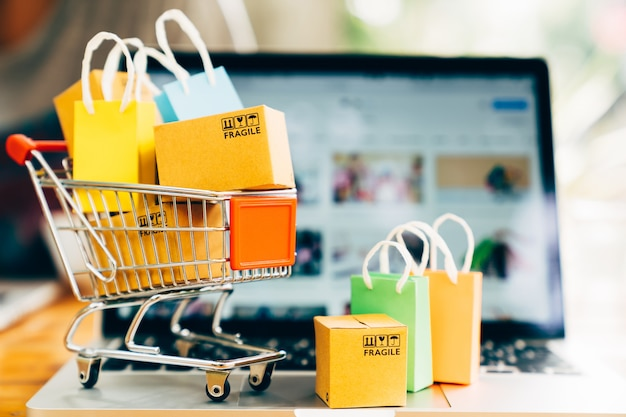 オンラインショッピングおよび配達の概念のためのラップトップとカートの製品パッケージボックスとショッピングバッグ   プレミアム写真