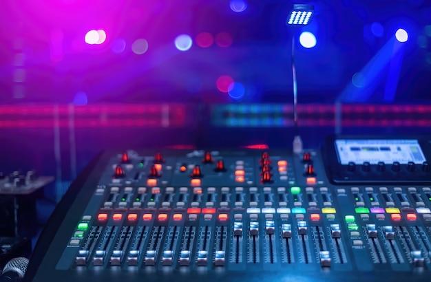 Production Concept 콘서트에서 음악 믹싱을위한 믹서에는 핑크와 블루 톤의 배경이 흐릿한 버튼이 많이 있습니다. 프리미엄 사진