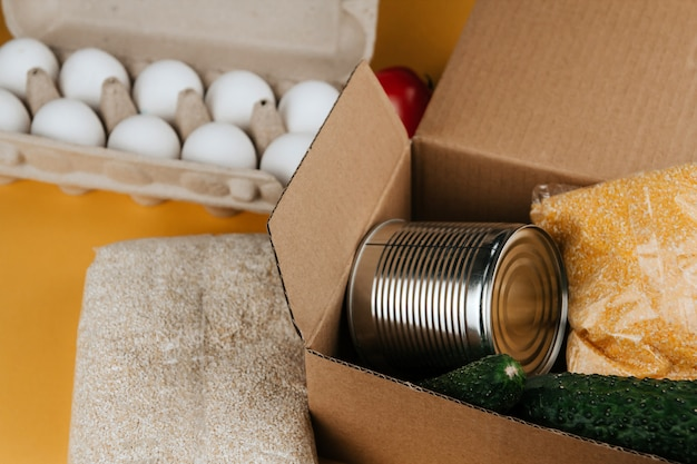 Products for donation on a yellow background. vegetables, cereals and canned food. food donations copy space. Premium Photo