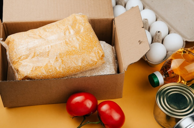 Products for donation on yellow. vegetables, cereals and canned food. Premium Photo
