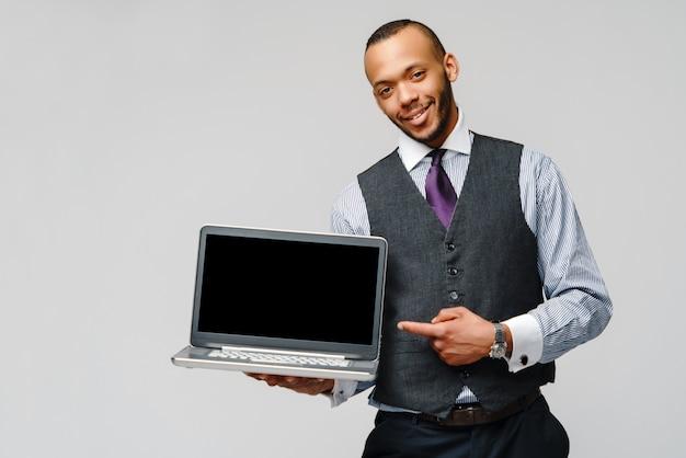 ラップトップコンピューターを保持しているプロのアフリカ系アメリカ人ビジネス男 Premium写真