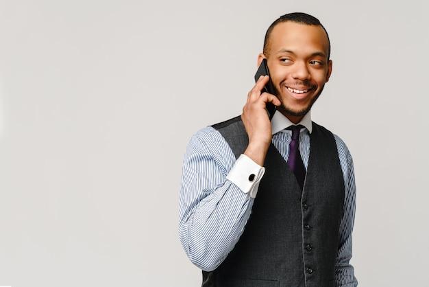 モバイル携帯電話で話しているプロのアフリカ系アメリカ人ビジネスの男性 Premium写真