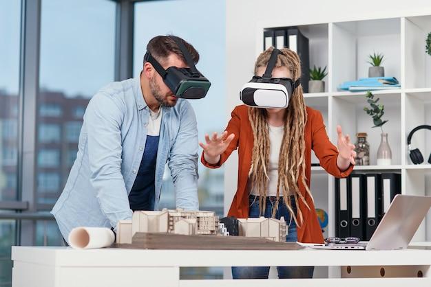 Профессиональный архитектор, работающий за офисным столом и одетый в гарнитуру vr, просматривает интерфейс виртуальной реальности. Premium Фотографии