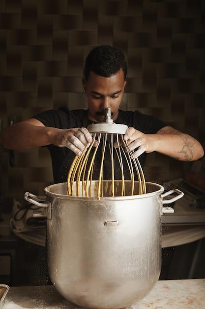 プロの職人菓子、黒人男性のチーフは、ブレンドされた卵と大きな鍋から大きな工業用泡立て器を取ります 無料写真